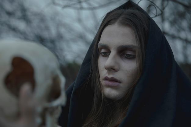 Uomo del primo piano che tiene un cranio vago