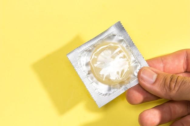 Uomo del primo piano che tiene un preservativo