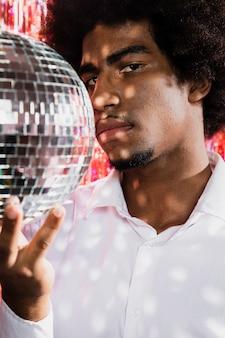 Uomo del primo piano che tiene una palla della discoteca