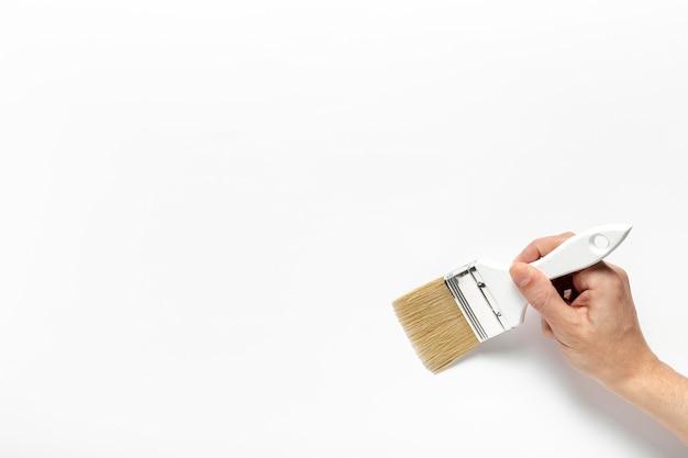 Uomo del primo piano che tiene una spazzola di pittura
