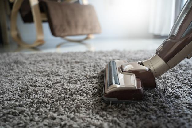 Uomo del primo piano che usando un aspirapolvere mentre pulendo nella stanza