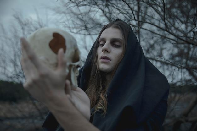 Uomo del primo piano con gli occhi chiusi che tengono un cranio