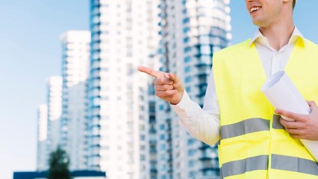 Uomo del primo piano con la maglia di sicurezza che indica a qualcosa
