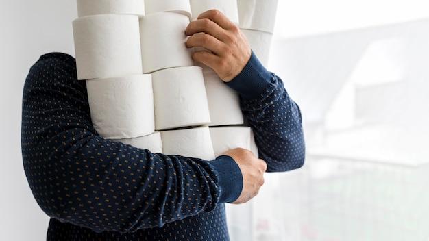 Uomo del primo piano con la pila di carta igienica