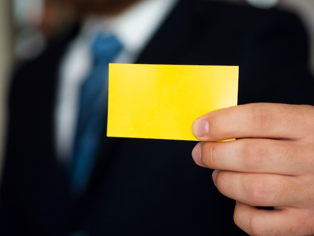 Uomo del primo piano in vestito con il biglietto da visita giallo