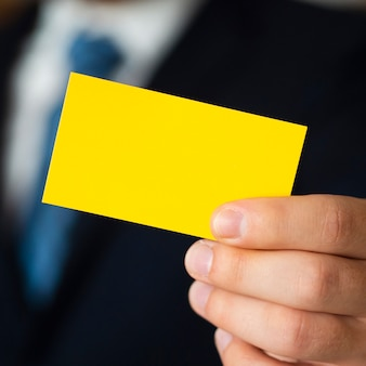 Uomo del primo piano in vestito con il biglietto da visita