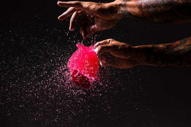 Uomo del primo piano schioccando un pallone con pittura rossa
