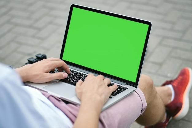 Uomo del programmatore che utilizza computer portatile nel parco