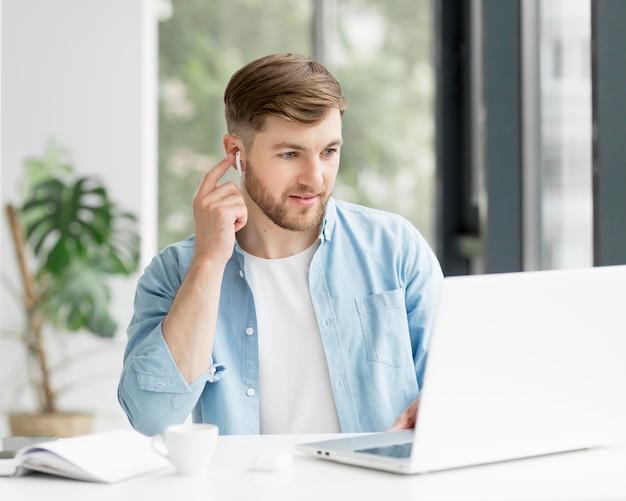 Uomo del ritratto con gli airpods che lavora al computer portatile