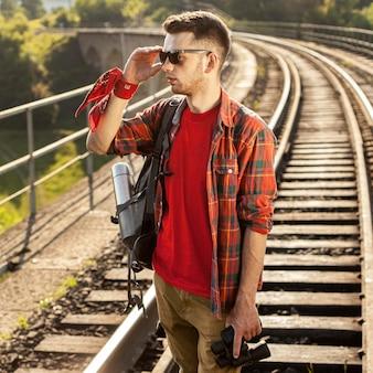 Uomo del ritratto con gli occhiali da sole al ponte con binoculare