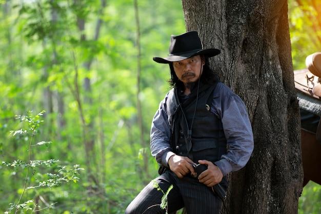 Uomo del ritratto con il cappello che fa una pausa l'albero come cowboy