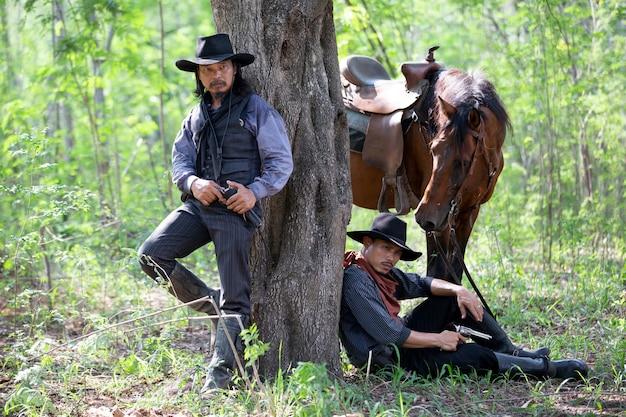 Uomo del ritratto con il cappello che fa una pausa l'albero con il cavallo come cowboy