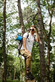 Uomo del ritratto con lo zaino in foresta