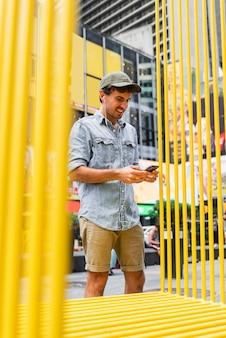 Uomo del ritratto nella città facendo uso del cellulare