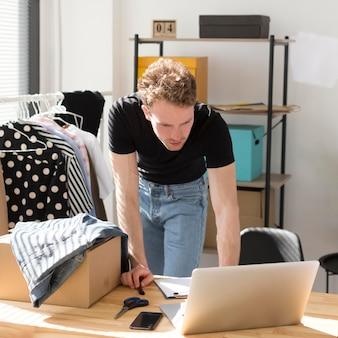 Uomo del tiro medio che esamina computer portatile