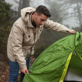 Uomo del tiro medio che mette su la sua tenda