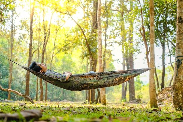 Uomo del viaggiatore che fa un'escursione e che si rilassa in amaca in legno di autunno