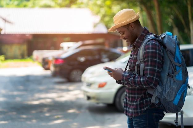 Uomo del viaggiatore che per mezzo dello smartphone al parcheggio e tenendo zaino