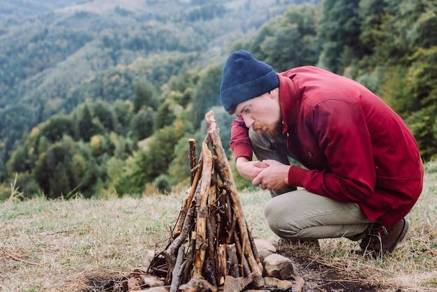 Uomo del viaggiatore che si siede vicino al fuoco