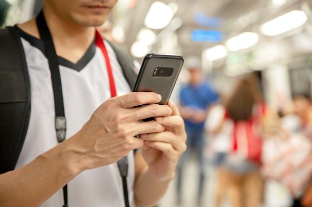 Uomo del viaggiatore che utilizza smartphone ad una stazione ferroviaria