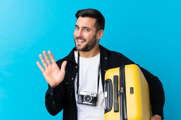 Uomo del viaggiatore con la barba sopra la parete isolata