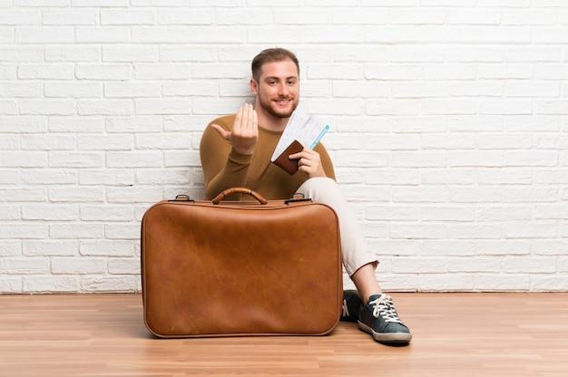 Uomo del viaggiatore con la valigia e la carta d'imbarco che invita a venire con la mano. felice che tu sia venuto