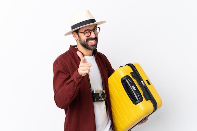 Uomo del viaggiatore con la valigia sopra la parete isolata
