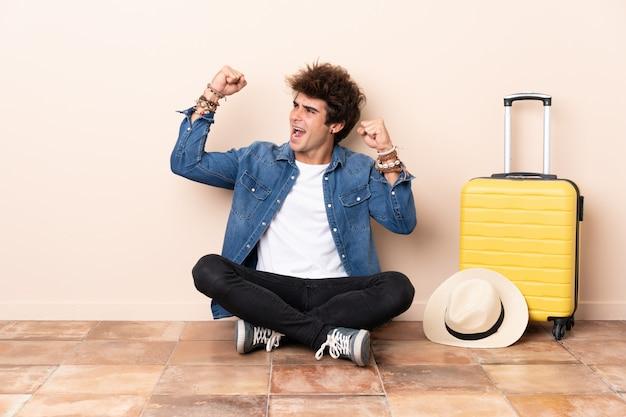 Uomo del viaggiatore con una valigia che si siede sul pavimento