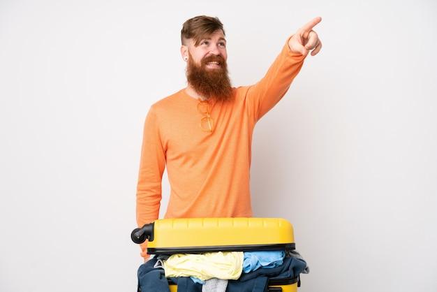 Uomo del viaggiatore con una valigia piena di vestiti sopra la parete bianca isolata che tocca sullo schermo trasparente