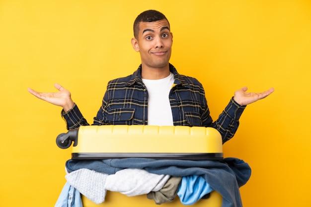 Uomo del viaggiatore con una valigia piena di vestiti sopra la parete gialla isolata che ha dubbi con l'espressione del viso confuso