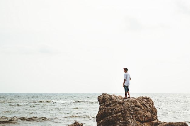 Uomo del viaggiatore sulla scogliera del mare