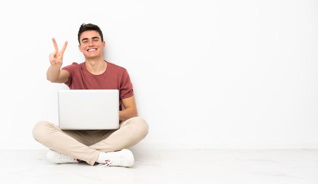 Uomo dell'adolescente che si siede su flor con il suo computer portatile che sorride e che mostra il segno di vittoria