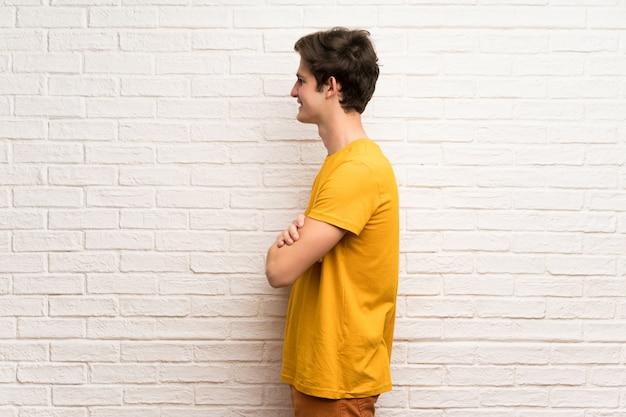 Uomo dell'adolescente sul muro di mattoni bianchi in posizione laterale