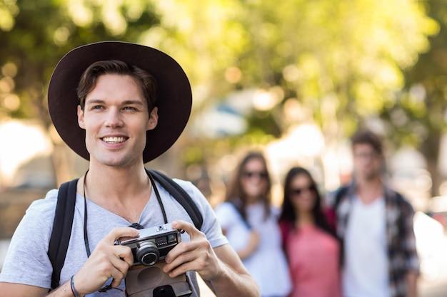 Uomo dell'anca con la macchina fotografica digitale che sorride all'aperto