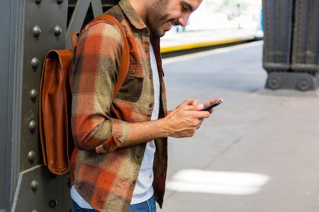 Uomo dell'angolo alto alla metropolitana facendo uso del telefono