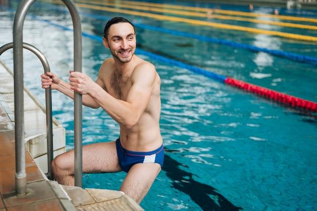 Uomo dell'angolo alto che esce dalla piscina