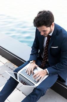 Uomo dell'angolo alto che lavora al computer portatile vicino al lago