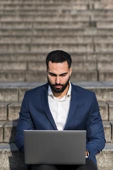 Uomo dell'angolo alto che lavora al computer portatile