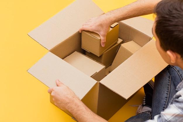 Uomo dell'angolo alto che organizza i pacchetti di consegna
