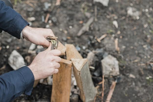 Uomo dell'angolo alto che organizza legno per il falò