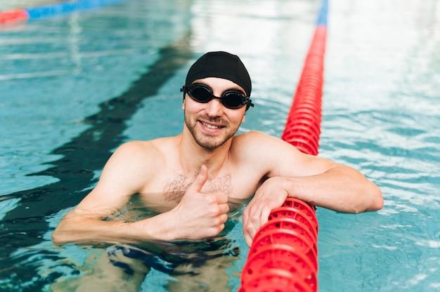 Uomo dell'angolo alto nella piscina che mostra segno giusto