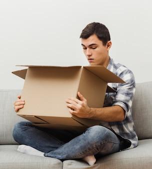 Uomo dell'angolo alto sorpreso del contenuto della scatola