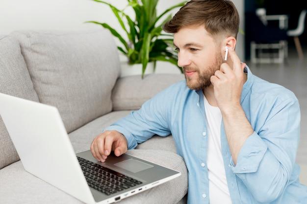 Uomo dell'angolo alto sul pavimento che lavora al computer portatile