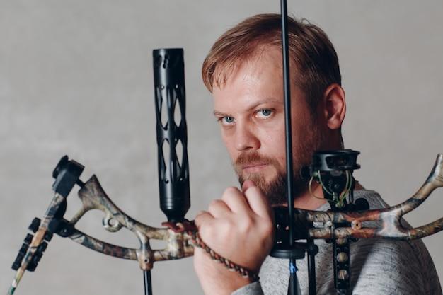 Uomo dell'arciere con l'arco e la freccia moderni di sport del blocco