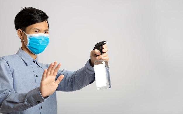 Uomo dell'asia che utilizza la pulizia dell'alcool dello spruzzo per proteggere i batteri anti virus. misure preventive contro il virus corona.