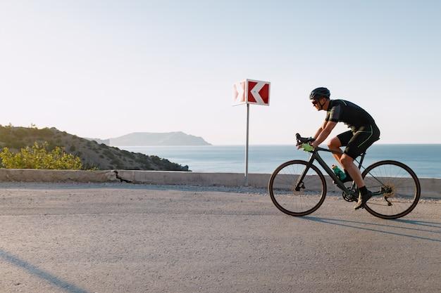 Uomo dell'atleta di sport di ciclismo che guida sulla strada costiera all'alba