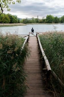 Uomo dell'avventuriero in una passerella su un lago