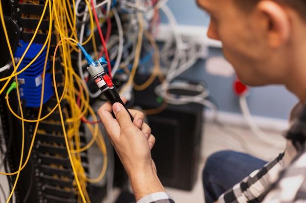 Uomo dell'ingegnere che collauda la fibra ottica