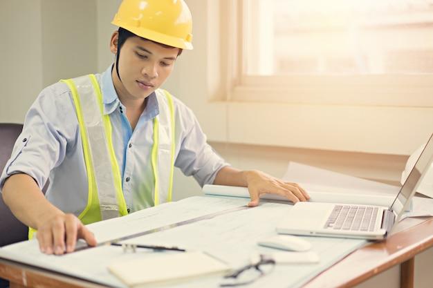 Uomo dell'ingegnere che lavora con il computer portatile e cianografie che schizzano un progetto di costruzione