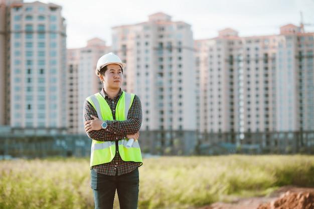 Uomo dell'ingegnere che lavora o che controlla al cantiere della costruzione